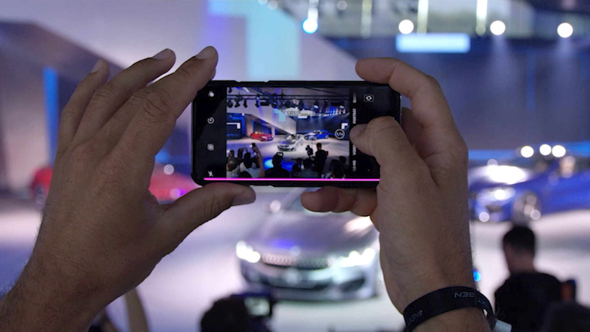 Taking a picture with a smartphone at a car tradeshow.